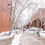 Students walk through the snow on the UWM campus.