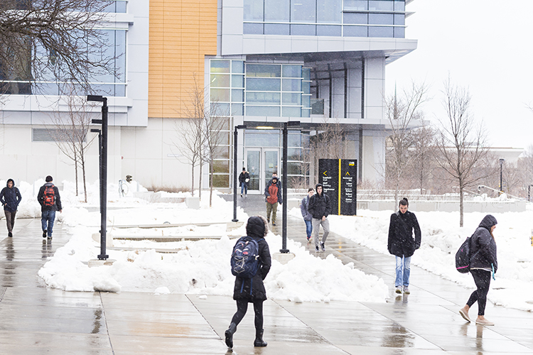 Snow falls as several students walk across the UWM campus.