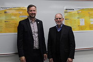 Two men stand in front of a whiteboard.