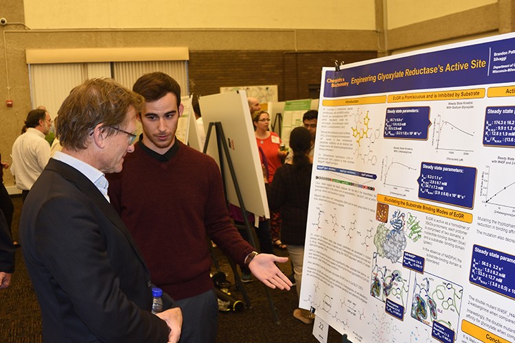 A student shows Feringa his poster presentation.
