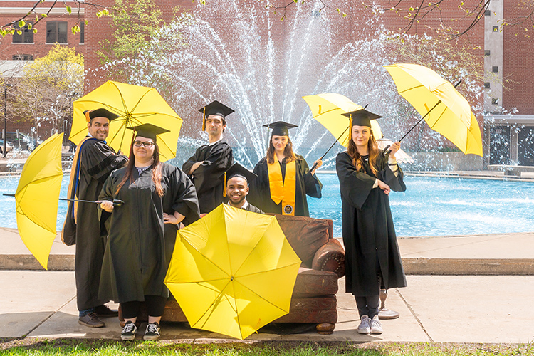 Graduates with umbrellas in front of UWM fountain