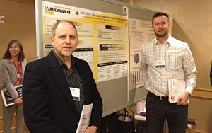Craig Berg and Ilya Avdeev stand in front of a presentation board.