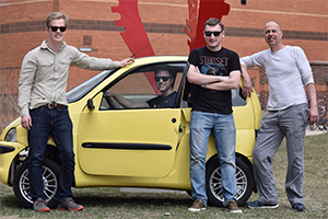 Four students stand in front of a small yellow car.