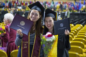Two women hold their diplomas up for a photo.