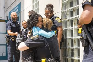 A girl hugs a police officer.