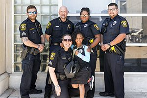 A girl poses with five police officers.