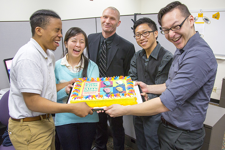Four people stand holding a cake.