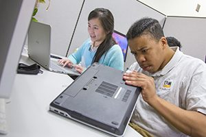 A student types on a computer while another attempts to repair a laptop.