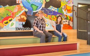 Two people sit on colorful bleachers against a background of a mural painted on a wall.