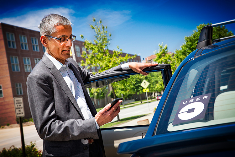 Man looks at his phone while getting into a car with an Uber sticker.