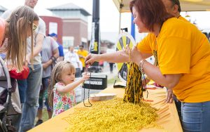 A woman in a yellow shirt hands a gold bead necklace to a small girl.