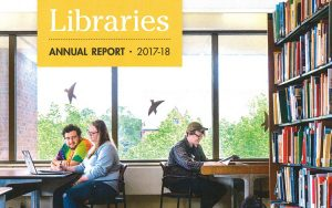 "Three people sit at tables by a window. There's a bookcase to their right. There's a yellow rectangle in the upper left corner with the text ""Libraries: Annual Report 2017-18."""