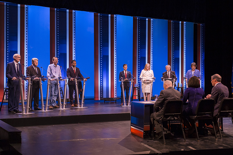 Eight people stand on stage facing three seated moderators.