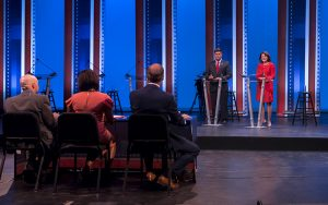 The two candidates stand onstage in front of podiums, while three debate moderators sit at a table with their backs tot he camera.