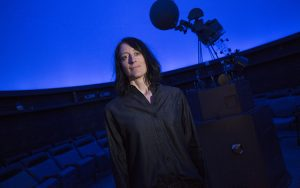 Dawn Erb stands in the planetarium with the projector in the background.