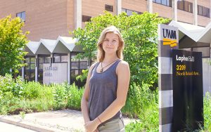 A student stands in front of a building at UWM.
