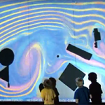 Children stand at a wall as a projection shows colorful lines depicting how a fluid would move.