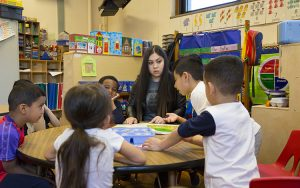 A teacher sits with several young students around a table.