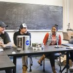 Four students sit at a table in a classroom.