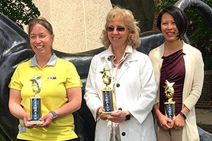 Three women stand holding trophies.