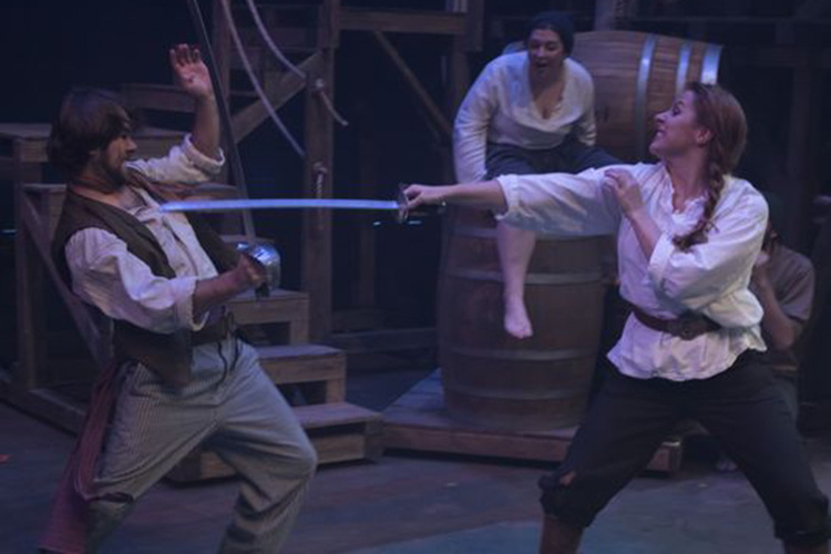 A man and women engage in an onstage sword fight.