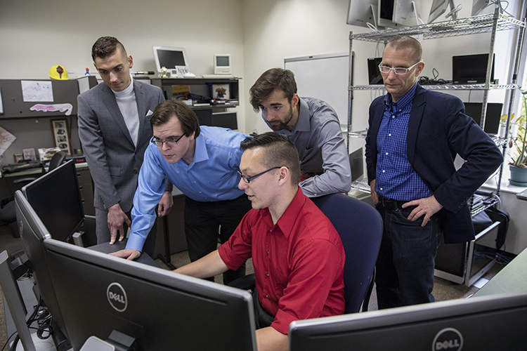 Five men work on a computer.