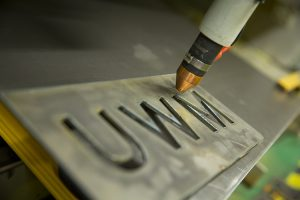 A piece of metal is carved with the initials UWM.