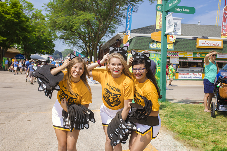 Three women hand out UWM material.
