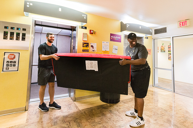 basketball coach and student move furniture