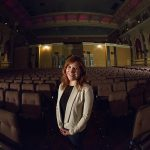 A woman stands amid rows of theater seats.