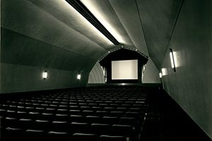 A long narrow auditorium of empty seats faces the screen.