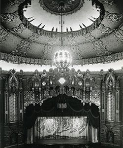 A chandelier hangs from the ceiling over a theater.