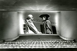 Two characters in colonial garb are shown on a movie screen.