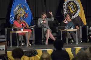 Three women sit on stage during a panel discussion.