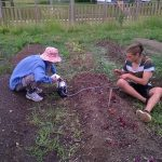 Two students sit on the ground working with plants.