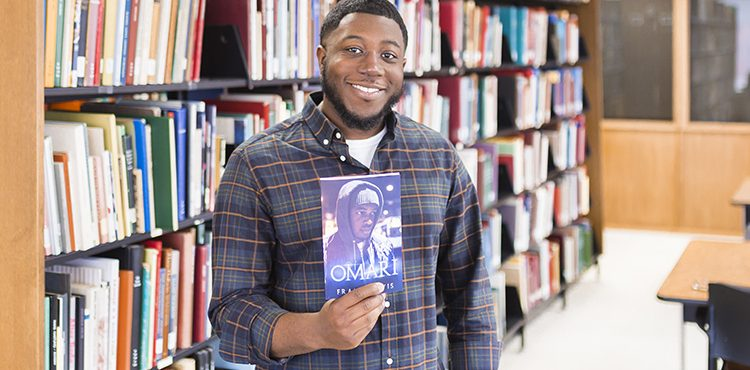 Frank Lewis holds up his book as he poses in a library.