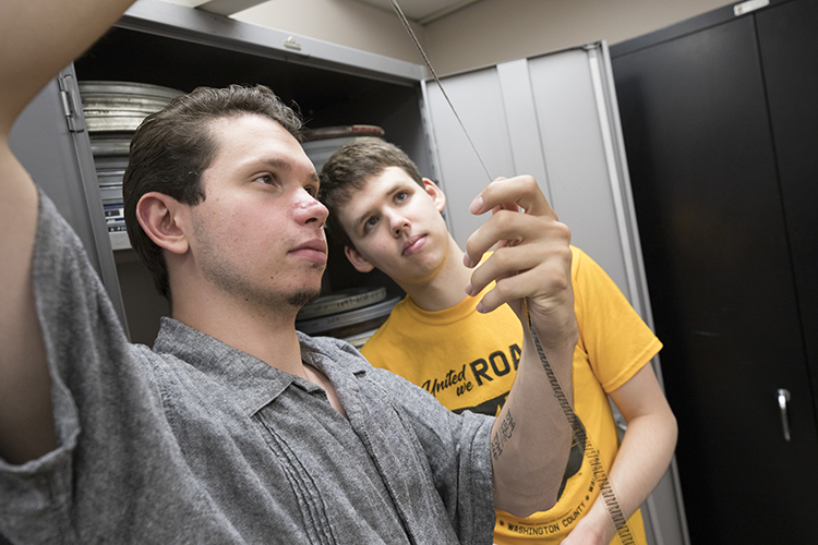 Students hold a strip of film up to the light while they look at it.