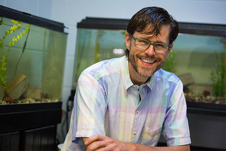 Mike Pauers poses in front of his aquariums.