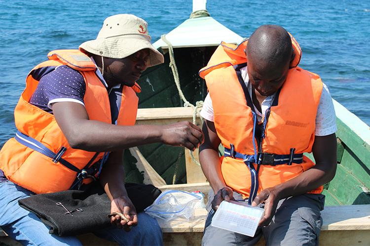 Two researchers from Malawi sit in a boat.