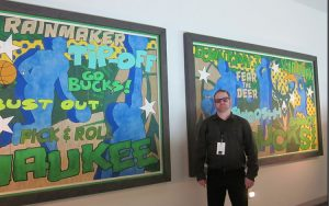 A man stands in front of two paintings.