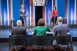 Two women stand on stage behind podiums.