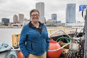 A woman stands aboard a ship on Lake Michigan with the Milwaukee skyline behind her.