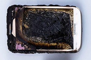 A Samsung smartphone lies burned and smashed.