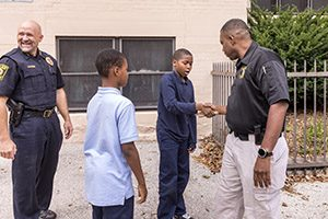 A student and police investigator shake hands outside a school.