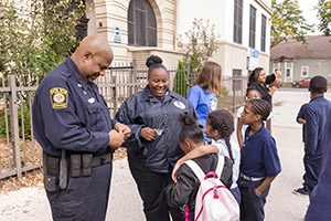 A police officer stands outside a school talking with students.