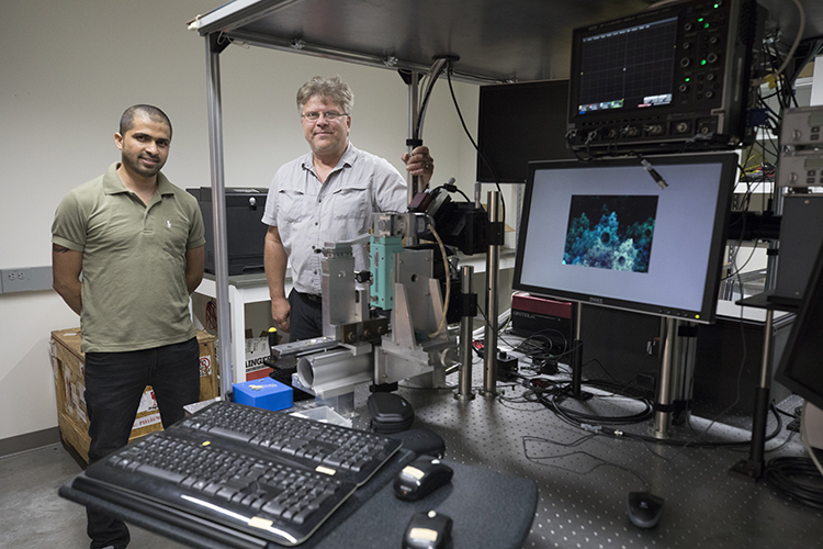 Two men stand in a lab full of equipment.