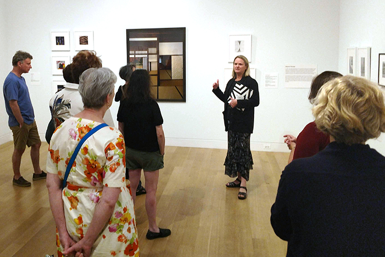 A woman stands in an art gallery talking to several visitors.