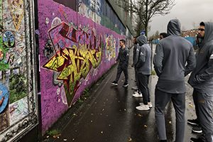A group of players look at a wall painted with graffiti.