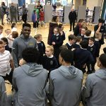 Basketball players sit on stage with their backs to the camera while elementary students sit on the floor and ask questions.