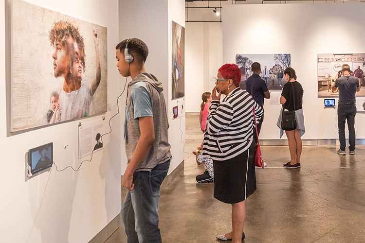 People look at artwork hanging on the walls of a gallery.